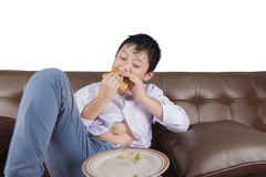 Little boy eats cheeseburger on couch Stock Photography