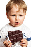 Little boy eats chocolate Stock Photos