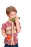 Little boy eats a cucumber Stock Photos
