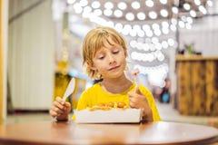 A little boy eats dessert waffles with jam in a cafe stock photos