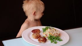 A little boy eats food in a cafe, close-up stock footage