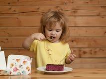 Little boy eats fruit cake Royalty Free Stock Images