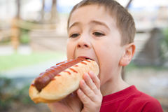 Little boy eats a huge hot-dog sandwich Stock Images