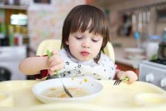 Little boy eats soup at home Stock Photos
