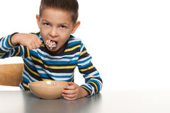 Little boy eats his breakfast Stock Photos