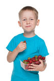 Little boy eats strawberry Stock Images