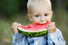Little boy eats watermelon Stock Images