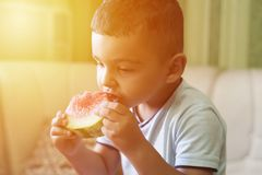 A Little Boy Eats Watermelon in the kitchen in Summer stock photo