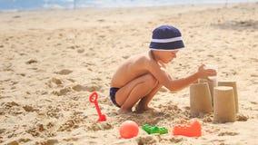 Little Boy em ocupas do chapéu remove a cubeta para fazer o bolo de areia video estoque