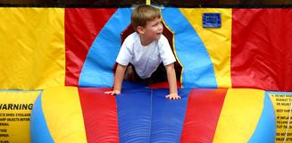 Little boy emerging from bounce house royalty free stock images