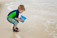 Little Boy en la playa con un compartimiento azul Foto de archivo