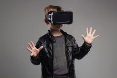 Little Boy en los vidrios de la realidad virtual que juegan al juego Embroma la diversión Fotografía de archivo