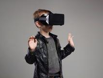 Little Boy en los vidrios de la realidad virtual que juegan al juego Embroma la diversión Fotos de archivo