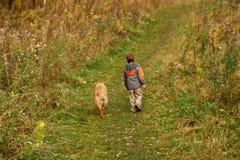 Little Boy en openlucht lopen van de Hond Stock Afbeelding