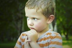 Little Boy en parc enfant humide après pluie Garçon beau avec des yeux bleus Image stock