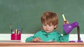Little Boy en sala de clase Lecciones de la escuela Peque?o muchacho preescolar lindo del ni?o en una sala de clase Poco childr e almacen de video