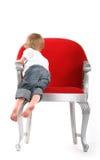 Little Boy en silla roja grande Imágenes de archivo libres de regalías