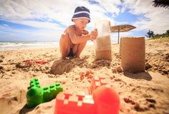 Little Boy en sombrero toca la arena en taza plástica en la playa cerca de los juguetes Fotos de archivo libres de regalías