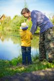 Little boy is engaged in fishing in a pond. Child with a dairy i. N his hands Royalty Free Stock Photo
