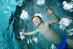 A little boy is engaged in sports swimming in the pool. Swims under water on a blue background and looks forward. Portrait. Shooting under water on a Royalty Free Stock Photo