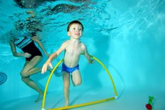 The little boy is engaged in sports, swims underwater at the bottom of the pool through the Hoop. Portrait. Shooting underwater from the bottom. Horizontal Stock Images