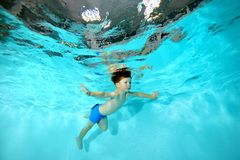 A little boy is engaged in underwater sports in the pool. Swims under water like a bird and looks forward. Portrait. Shooting underwater at the bottom Stock Photography