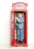 Little boy in English red phone Stock Images