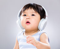 Little boy enjoy listen to music. On grey color background Stock Photography