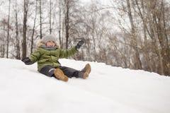 Little boy enjoy riding on ice slide in winter stock photos