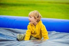 Little boy enjoying jumping on trampoline summer day outside stock photo