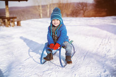 Little boy enjoying a sleigh ride. Child sledding. Toddler kid r. Iding a sled. Children play outdoors in snow. Kids sled in winter park. Outdoor active fun for Royalty Free Stock Images
