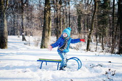Little boy enjoying a sleigh ride. Child sledding. Toddler kid riding a sled. Children play outdoors in snow. Kids sled in winter park. Outdoor active fun for Royalty Free Stock Photo