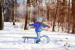 Little boy enjoying a sleigh ride. Child sledding. Toddler kid riding a sled. Children play outdoors in snow. Kids sled in winter park. Outdoor active fun for Stock Image