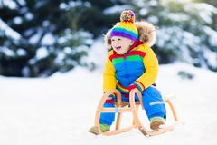 Boy on sleigh ride. Child sledding. Kid with sledge. Little boy enjoying a sleigh ride. Child sledding. Toddler kid riding a sledge. Children play outdoors in Stock Images