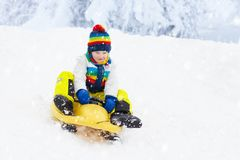 Little boy enjoying a sleigh ride. Child sledding. Toddler kid riding a sledge. Children play outdoors in snow. Kids sled in the. Alps mountains in winter royalty free stock photos