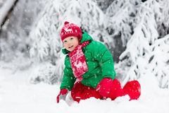 Little boy enjoying a sleigh ride. Child sledding. Toddler kid riding a sledge. Children play outdoors in snow. Kids sled in the royalty free stock photo