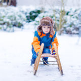 Little kid boy enjoying sleigh ride in winter. Little boy enjoying sleigh ride during snowfall. Child sledding on snow. Preschool kid riding a sledge. Child play Stock Photos