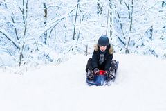 Little boy enjoying a sleigh ride in a snowy forest Royalty Free Stock Photo
