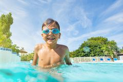 Little boy enjoying summer playing in the pool Stock Photos