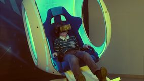 Little boy enjoying virtual reality in a moving interactive chair. Professional shot in 4K resolution. 093. You can use it e.g. in your commercial video Royalty Free Stock Image