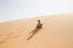 Little boy enjoys the warm sand sitting on a dune Royalty Free Stock Photo