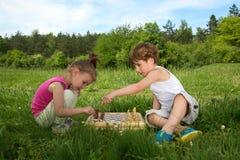 Little Boy enseignant à son amie comment jouer aux échecs dehors Images libres de droits