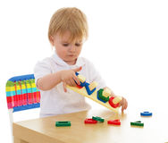 Little boy enthusiastically working with Montessori materials Royalty Free Stock Photos