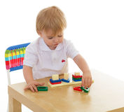 Little boy enthusiastically working with Montessori materials Stock Photos