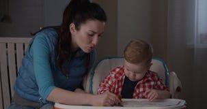 Little Boy está aprendiendo con la madre dibujar con los lápices coloreados metrajes
