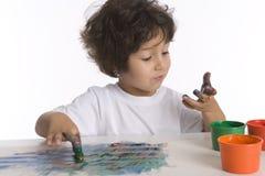 Little Boy está olhando sua mão completamente da pintura Imagens de Stock Royalty Free