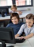 Little Boy et fille à l'aide du PC de bureau Image stock