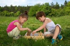 Little Boy et fille s'asseyant sur l'herbe et apprenant comment jouer aux échecs la belle journée de printemps Images stock
