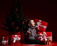 Little boy on the eve of new year and christmas is sitting under the tree. A surprised little boy on New Year`s Eve and Christmas is sitting under the Christmas stock photography