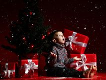 Little boy on the eve of new year and christmas is sitting under the tree. A surprised little boy on New Year`s Eve and Christmas is sitting under the Christmas royalty free stock images
